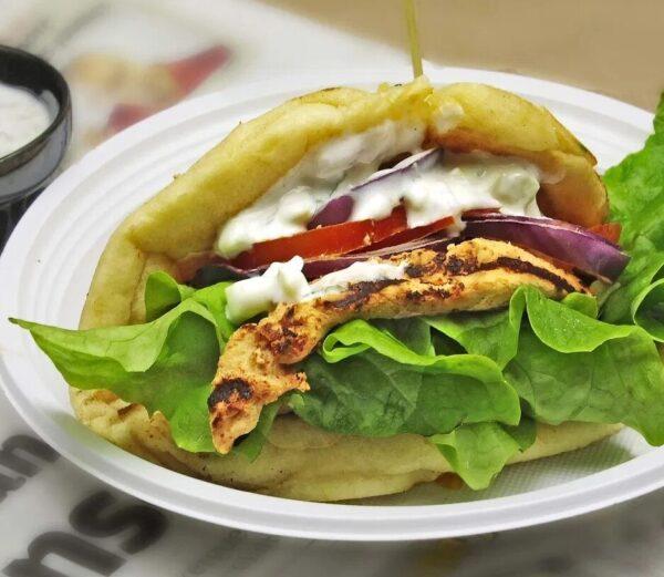 Sandwich au poulet tandoori et raïta sur pain naan et ses garnitures